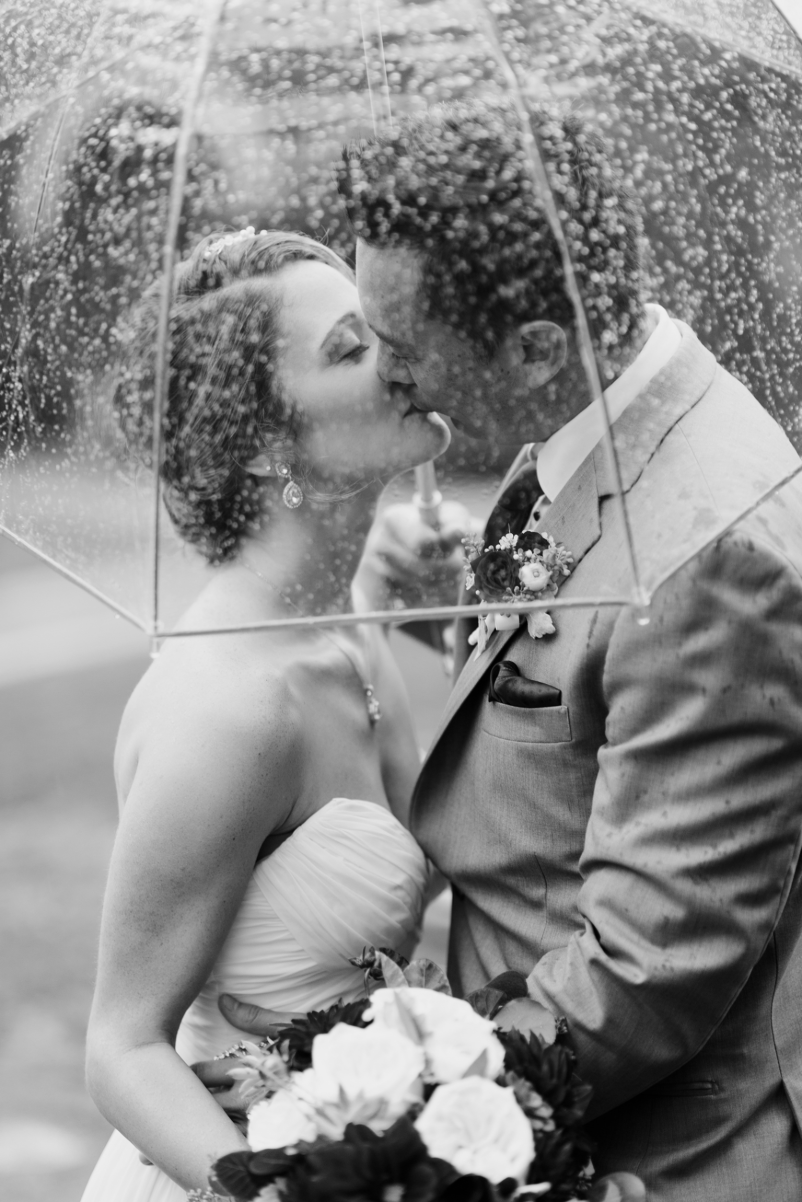 black and white of couple kissing under umbrella on wedding day